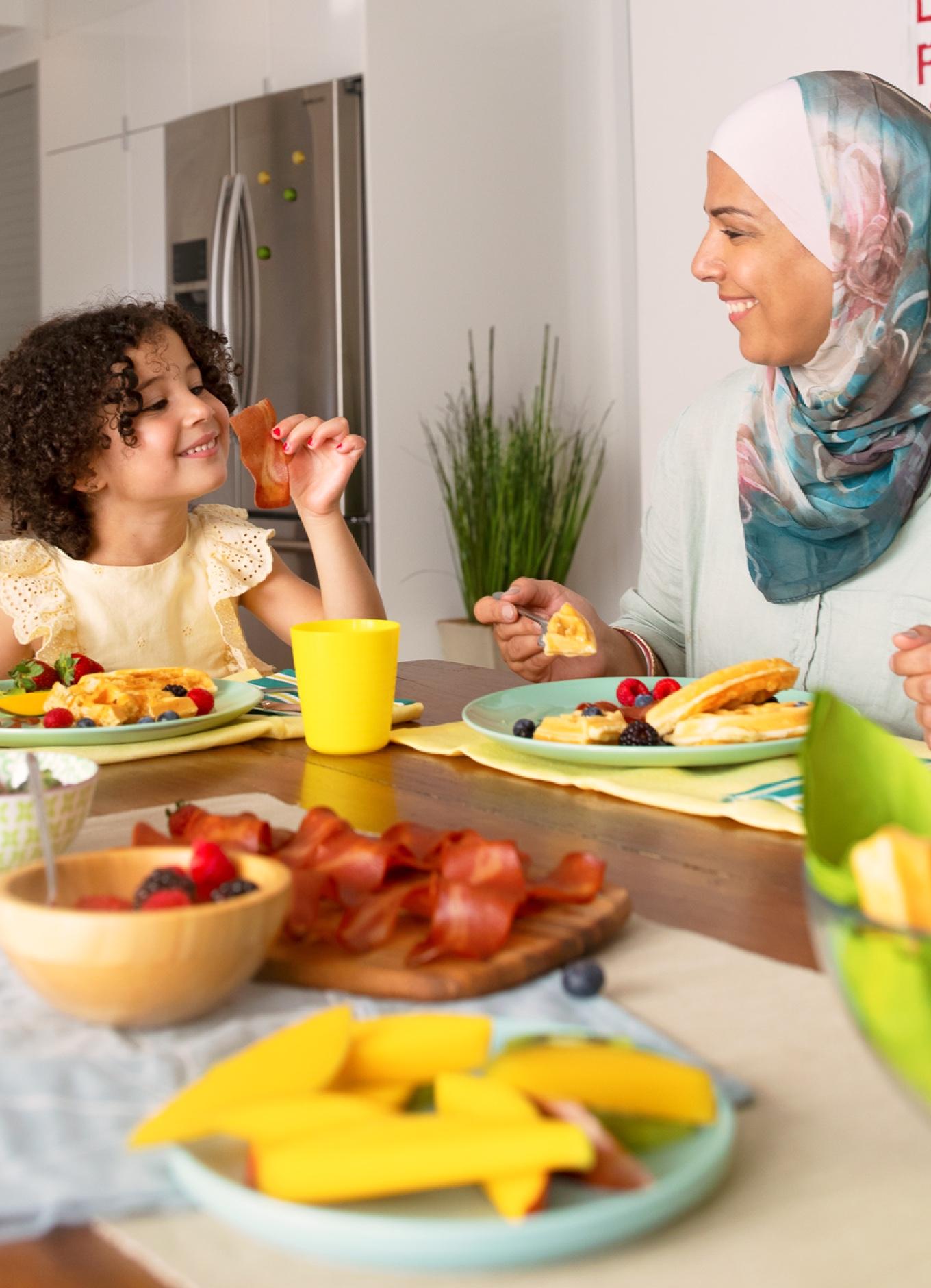 Une mère et son enfant savourant du bacon au poulet halal et des fruits frais.