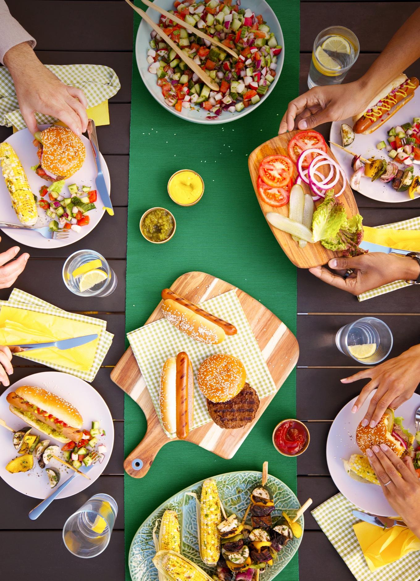 Une table de jardin dressée pour un barbecue, avec assiettes de hamburgers, de maïs grillé et d'accompagnements.