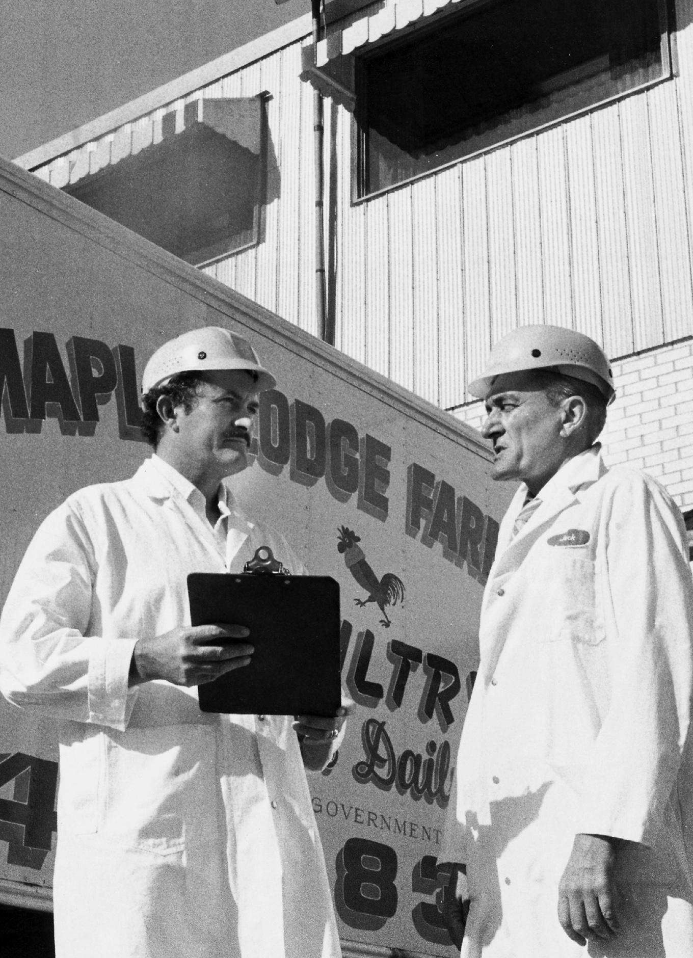 Une photo de deux employés de Maple Lodge Farms à côté d'un truc des années 60.