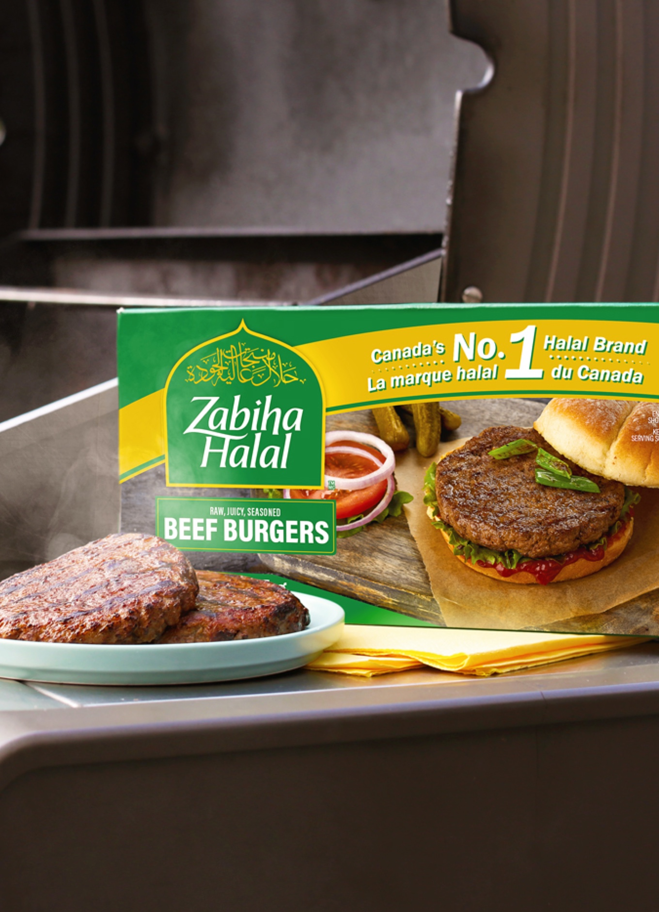 A package of Zabiha Halal beef burgers beside a plate of patties on a barbecue